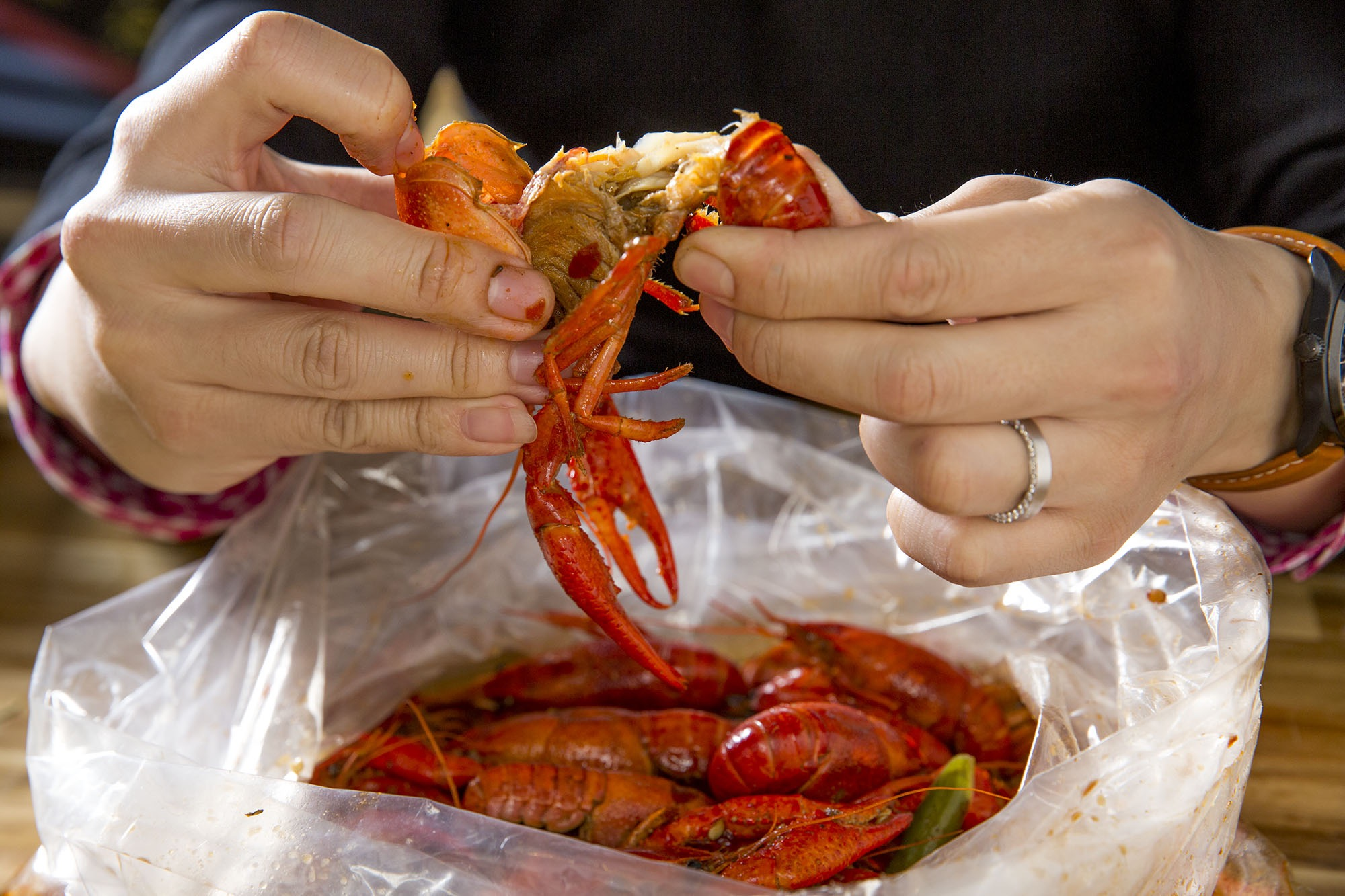 Hands pulling apart crawfish at a Chinese Restaurant